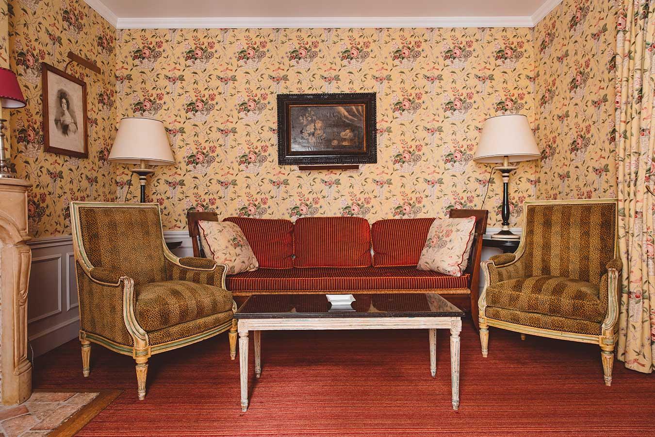 Appartement Terrasse - Canapé rouge, fauteuils à motif léopard beige et table basse dans une harmonie fleurie jaune