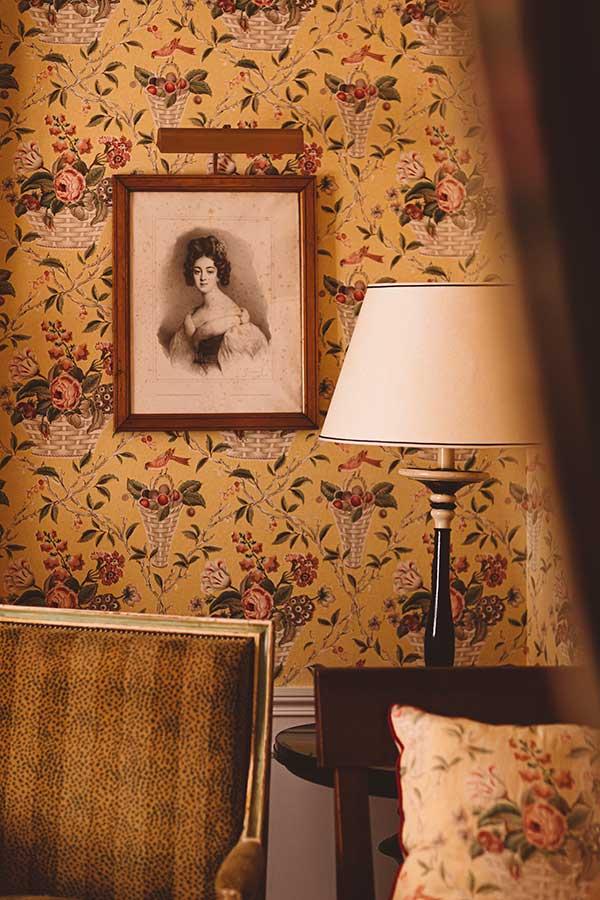 Appartement Terrasse - Coin salon avec fauteuil motif léopard beige, lampe et cadre sur un papier peint fleuri jaune