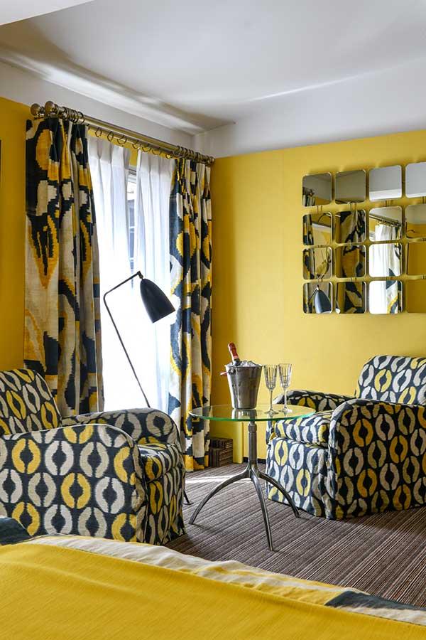Junior Suite Jardin - Coin salon avec sceau à champagne et deux coupes sur une table basse ronde en verre, deux fauteuils aux motifs géométriques noir, jaune et gris, rideaux assortis