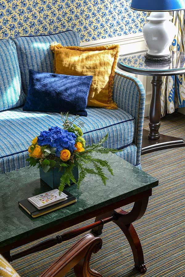 Appartement Terrasse - Table basse en marbre vert avec bouquet de fleurs, canapés et coussins dans les tons jaune et bleu