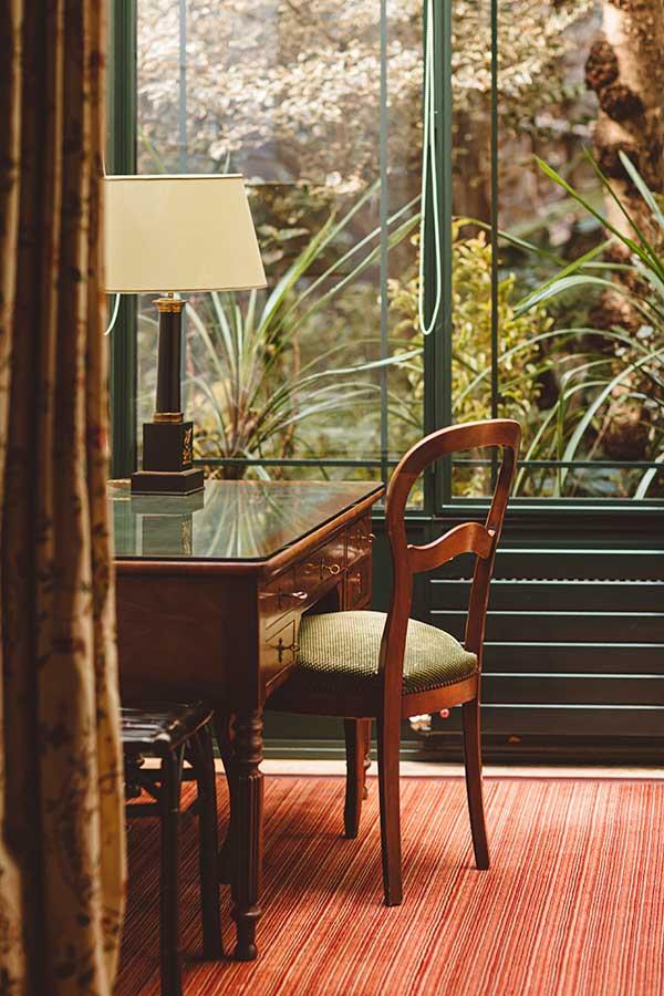 Junior Suite Jardin - Bureau en bois avec chaise, lampe et rideau, sous une verrière avec fond végétal