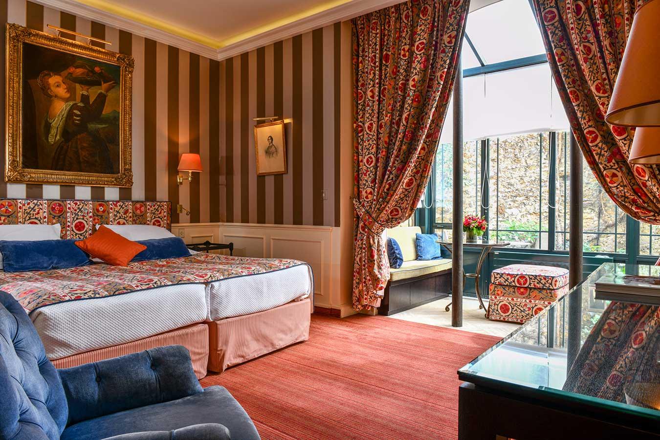 Junior Suite Jardin - vue chambre avec lit en configuration twin dans les tons rouge et bleu, verrière ensoleillée avec canapés et bureau en bois foncé à droite