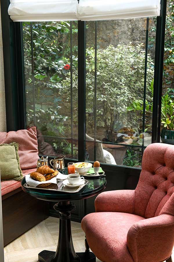 Junior Suite Jardin - Canapé rose et coussin vert avec petit-déjeuner sur table ronde sous la verrière ensoleillée