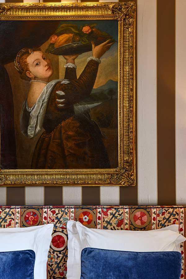 Junior Suite Jardin, tableau sur fond à rayures verticales blanches et marron, tête de lit à motifs dans les tons bleu et rouge