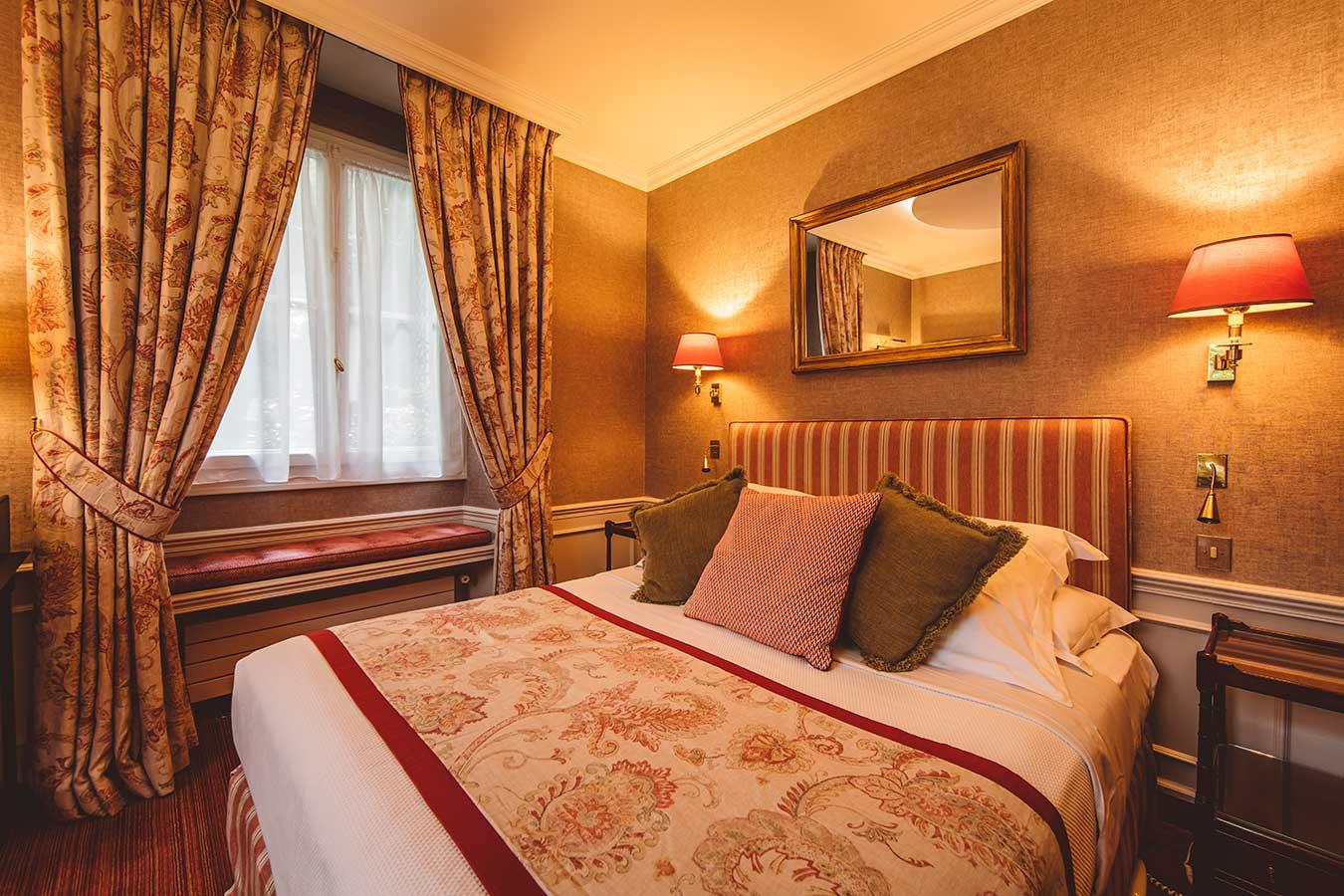 Junior Suite Jardin - Grand lit et banquette de fenêtre, rideaux à motifs, harmonie rouge et beige