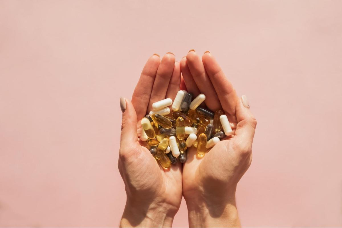 best time to take magnesium: woman holding a lot of pills