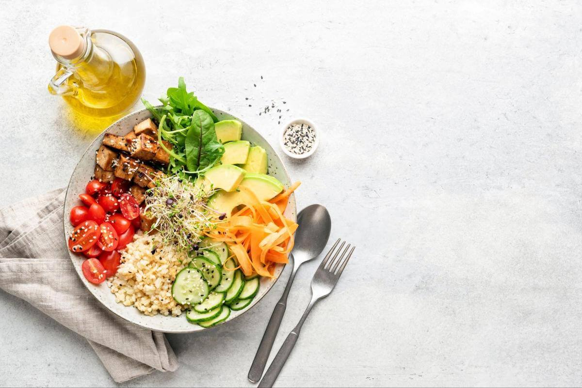 Normal blood sugar levels: A bowl of rice and vegetables sitting on a table with utensils and a bottle of olive oil