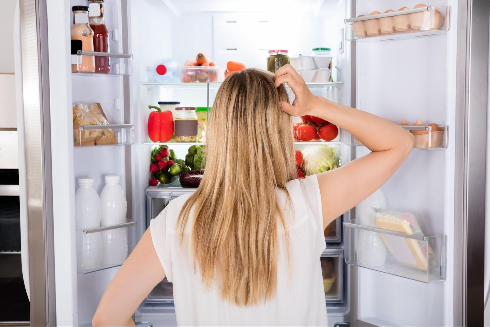 pros and cons of intermittent fasting: woman looking at the contents of her fridge