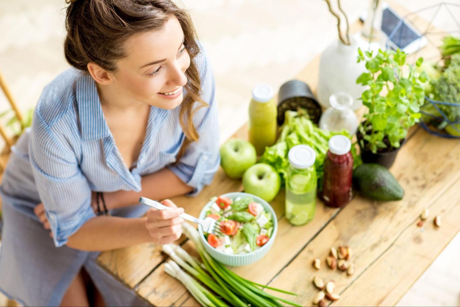 pros and cons of intermittent fasting: woman happily eating salad
