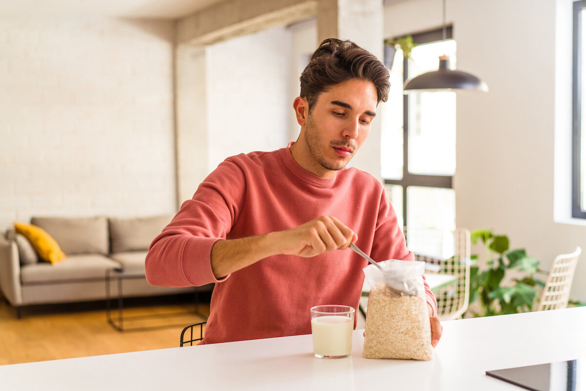 Foods with high thermic effect: man eating oats and a glass of milk