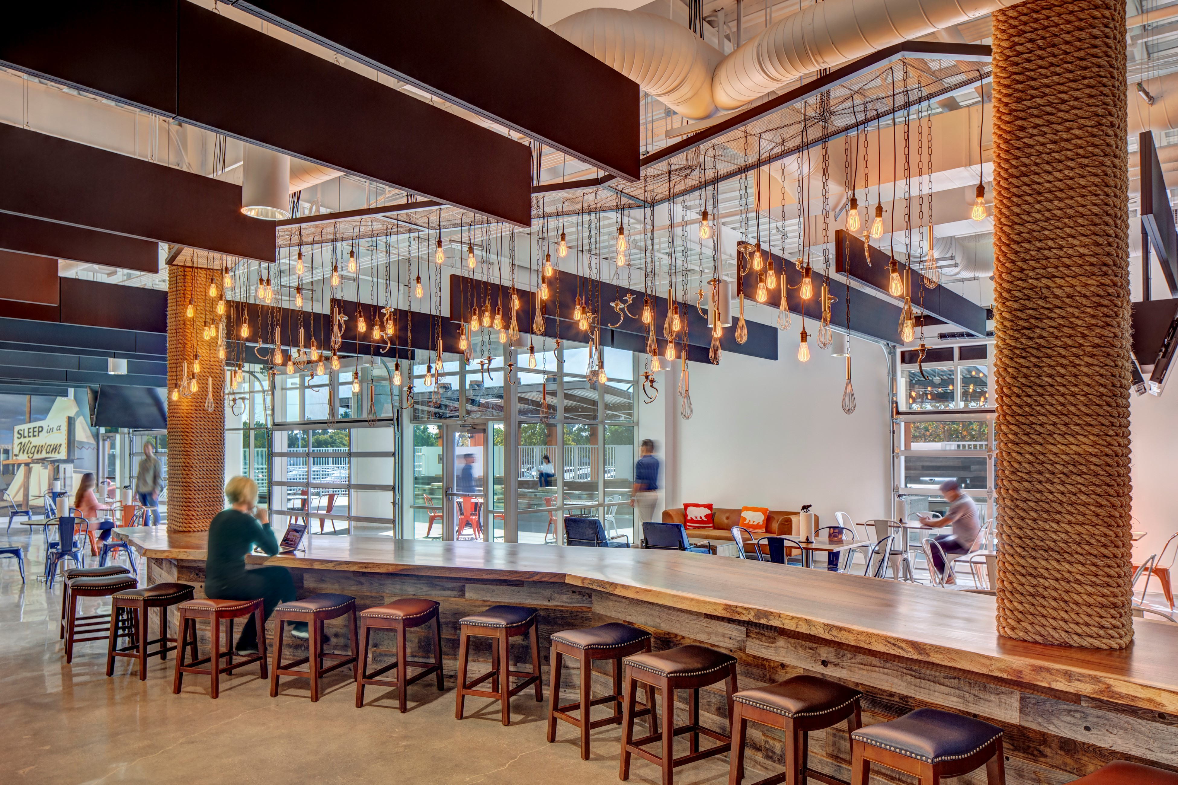 Lighting Design Services for Behr Headquarters. a variety of vintage light bulbs and fixtures hand over a wooden bar top.