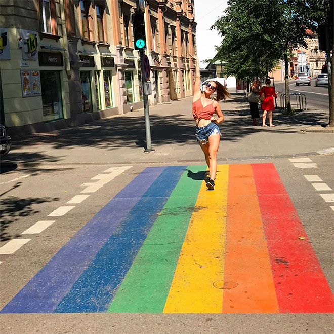 Woman crossing street on rainbow colored crosswalk