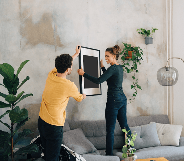 A young couple hanging up a picture.