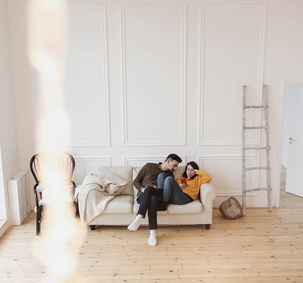 TX Markets Homegate brand image. A couple playfully interacting on a couch.