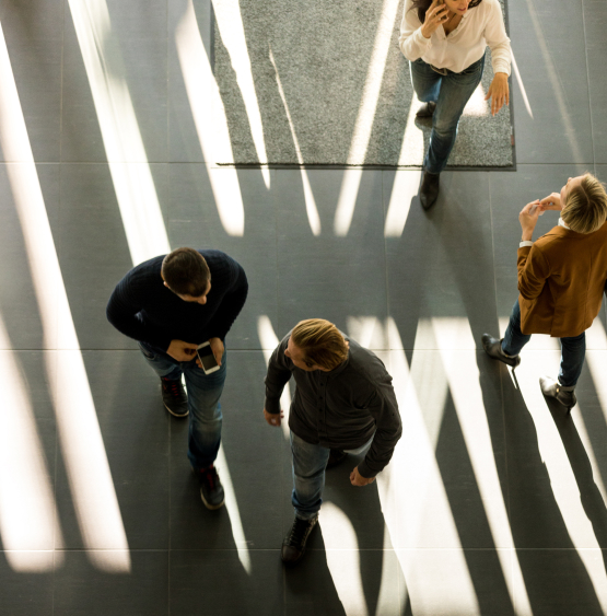 Bird view image of different people walking around in an office space