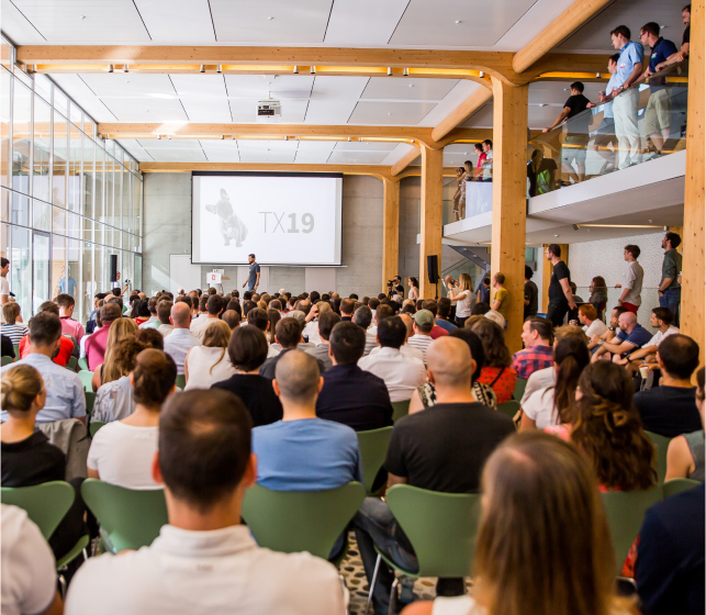 A crowd watching a keynote at the 2020 TX Marketing Conference in Zurich