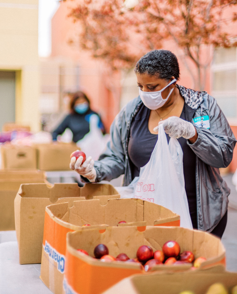 Woman collecting food at a food drive.