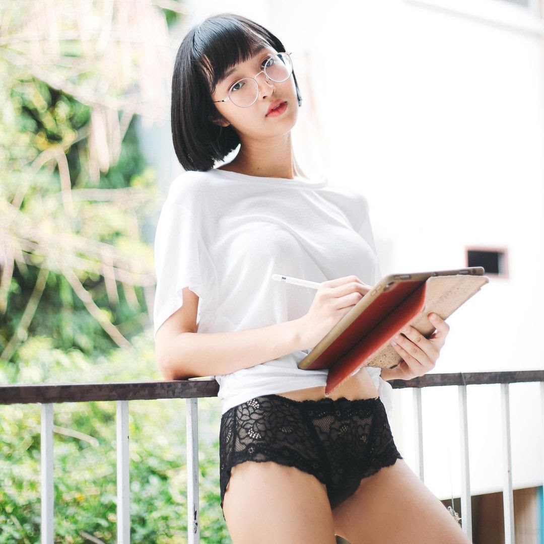 Thai female OnlyFans creator Deerlong with a white top black panties and holding an ipad