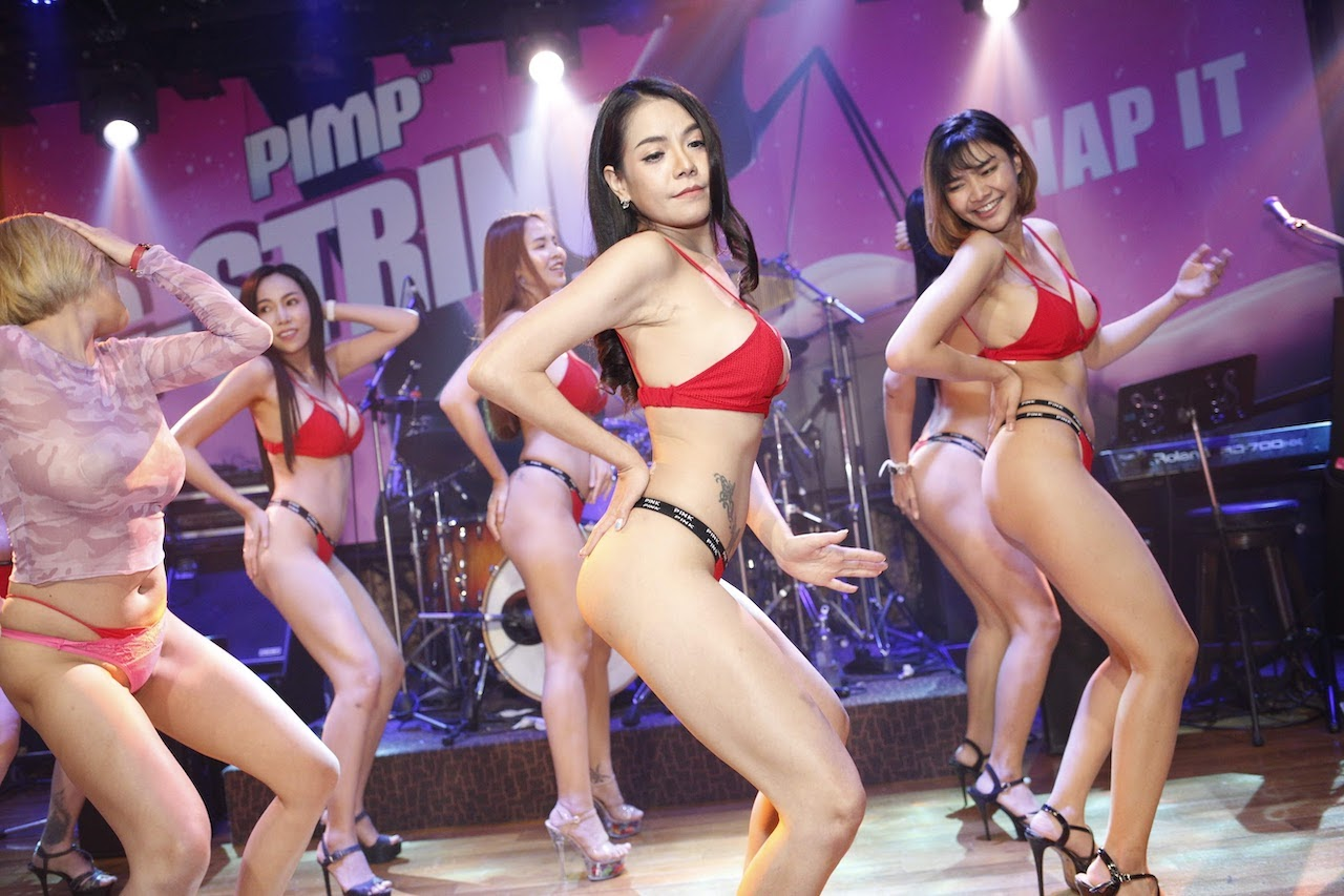 sexy show on stage of The PIMP Bangkok performed by hot Thai modes in red bikinis