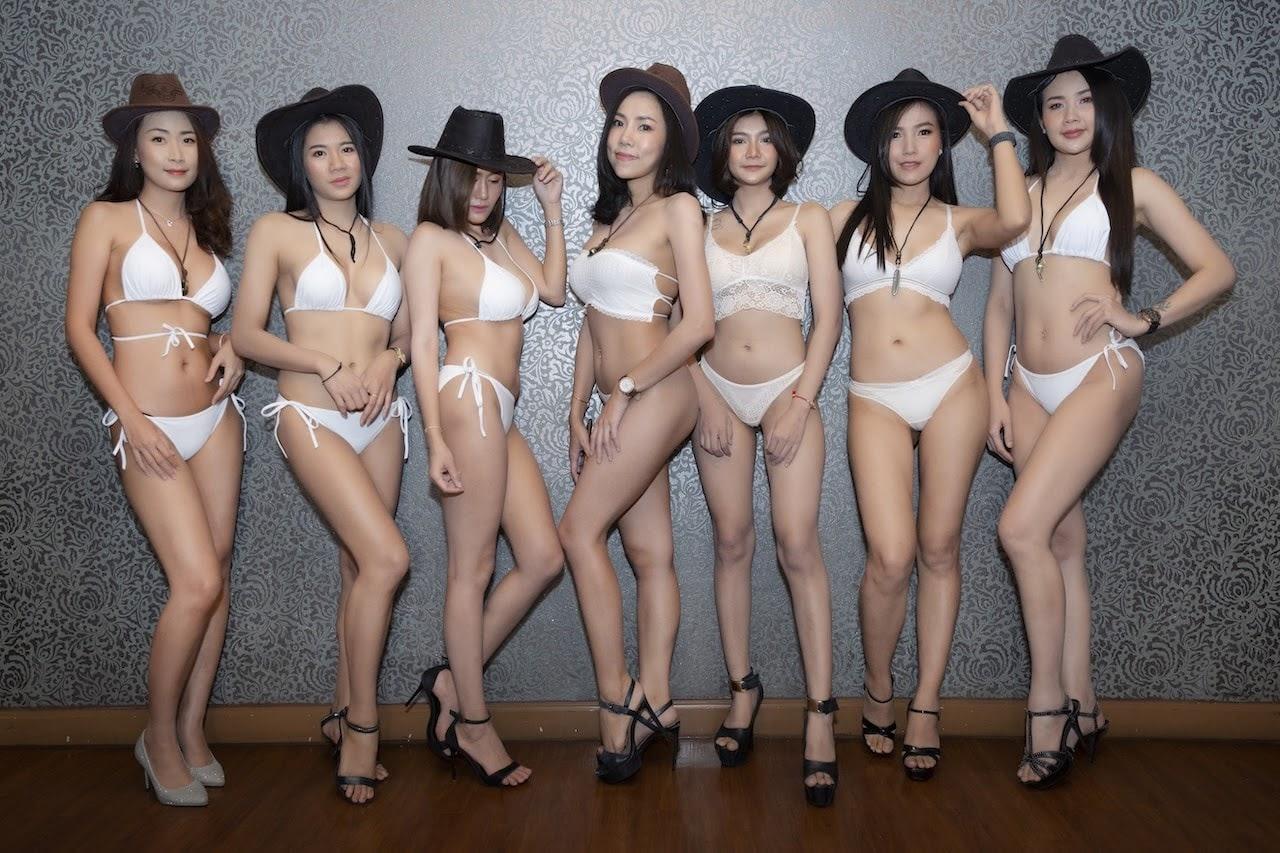 hot Thai models from a gentlemen club in Bangkok wearing white bikinis and cowboy hats
