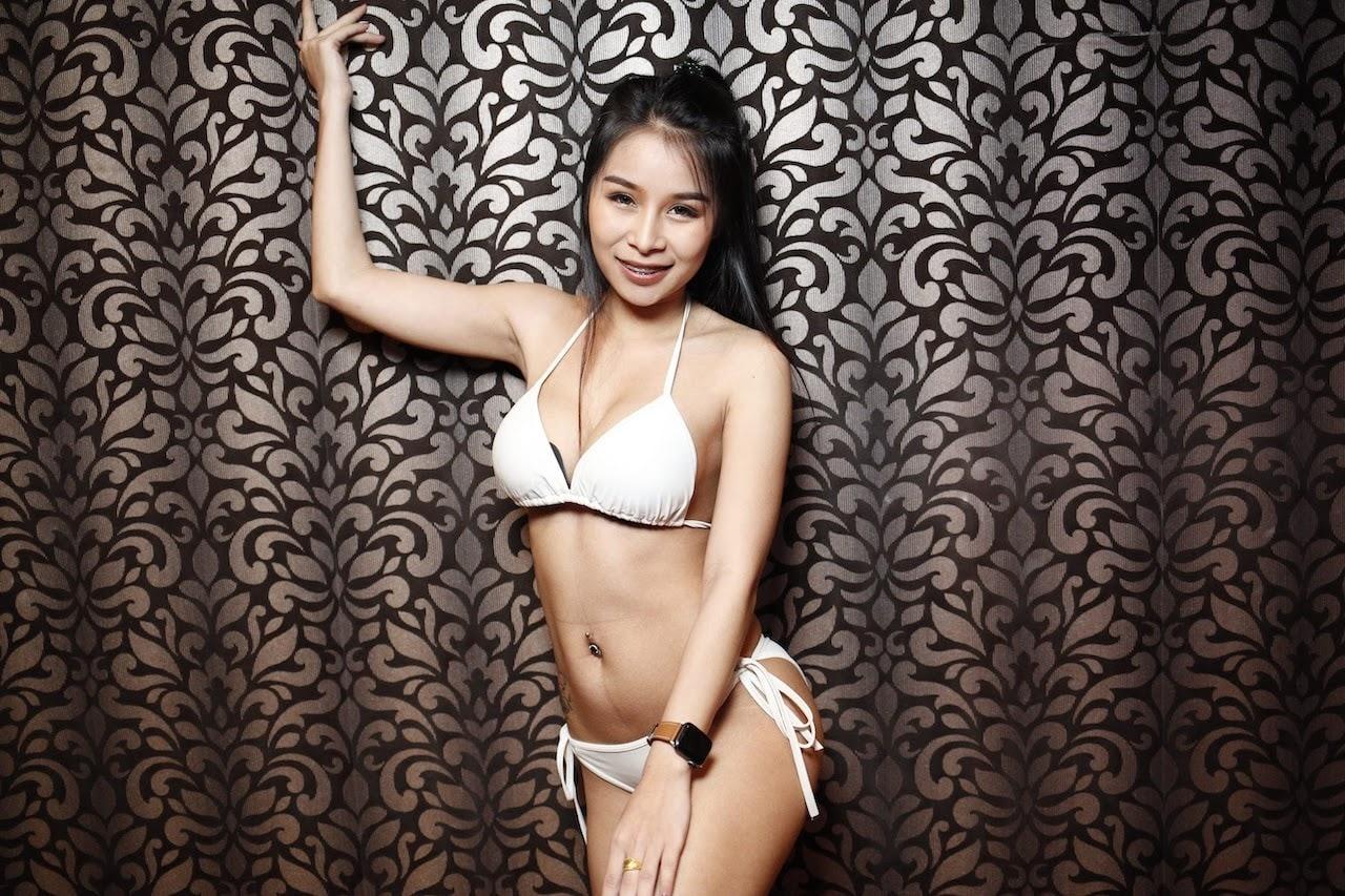 Thai bikini model at The PIMP club against a grey and black wall