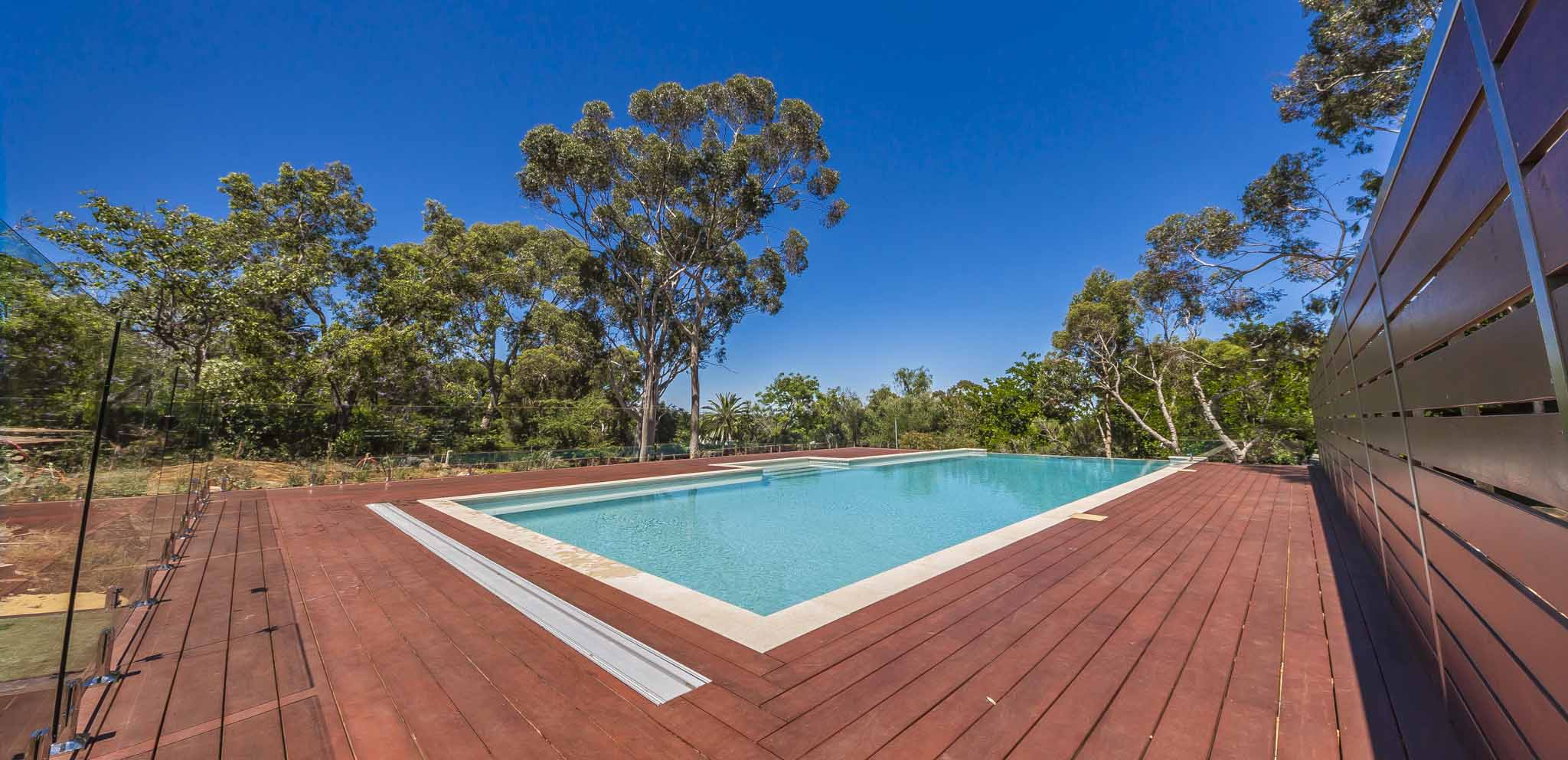 pool and deck with trees