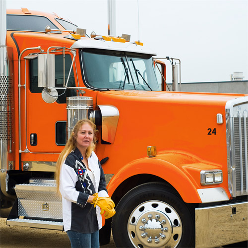 woman trucker in front of truck. freight dispatch services.