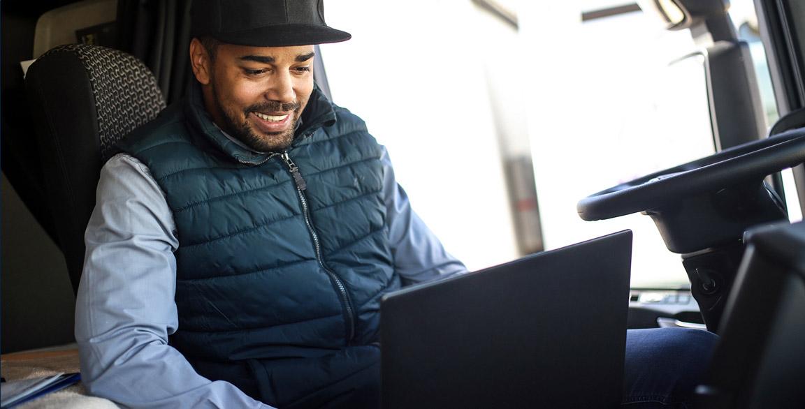 trucker booking loads on laptop