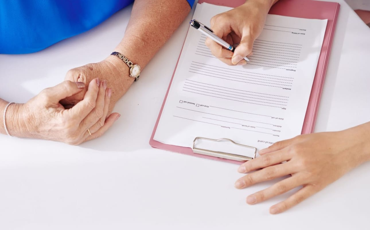 Doctor writing on patient chart