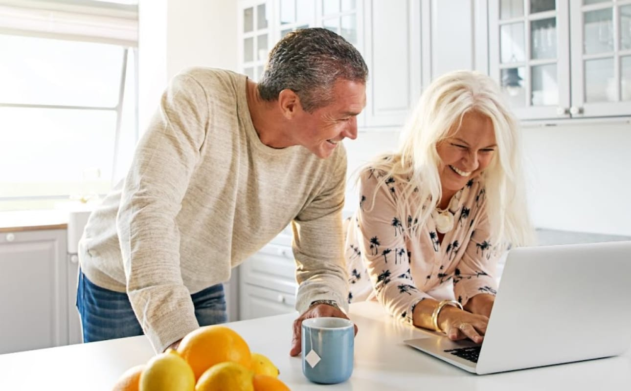 Senior couple relaxing the a kitchen with a laptop
