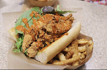 Catfish Po' Boy comes with lettuce, pickles, tomatoes, & your choice of sauce, loaded on top of a French roll or Texas toast.