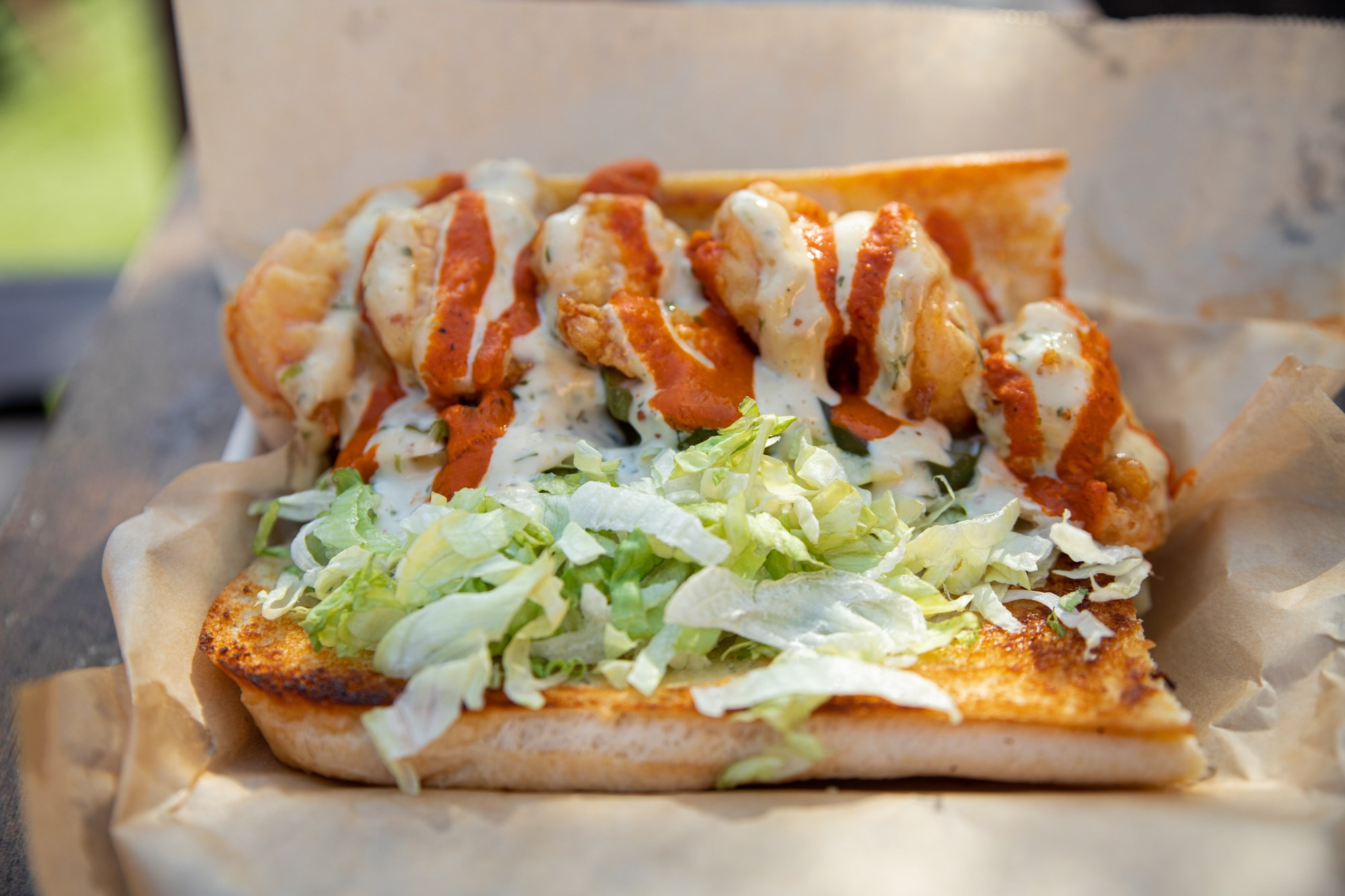 Shrimp Po' Boy comes with lettuce, pickles, tomatoes, & your choice of sauce, loaded on top of a French roll or Texas toast.