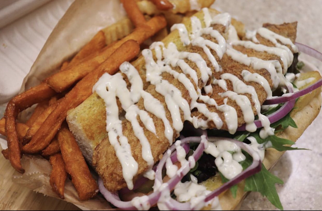Tilapia Po' Boy comes with lettuce, pickles, tomatoes, & your choice of sauce, loaded on top of a French roll or Texas toast.