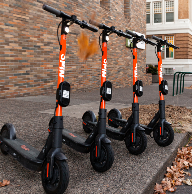 Four Spin electric scooters parked in a row on the sidewalk in front of a red brick wall