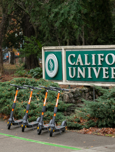 Four Spin electric scooters parked in front of a wooded college campus entrance