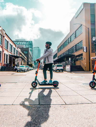 Casually-dressed young man wearing a helmet and riding a Spin electric scooter across a city street