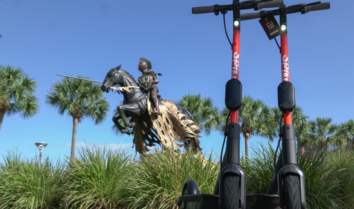 Two Spin electric scooters parked in front of the University of Central Florida's Charging Knight statue