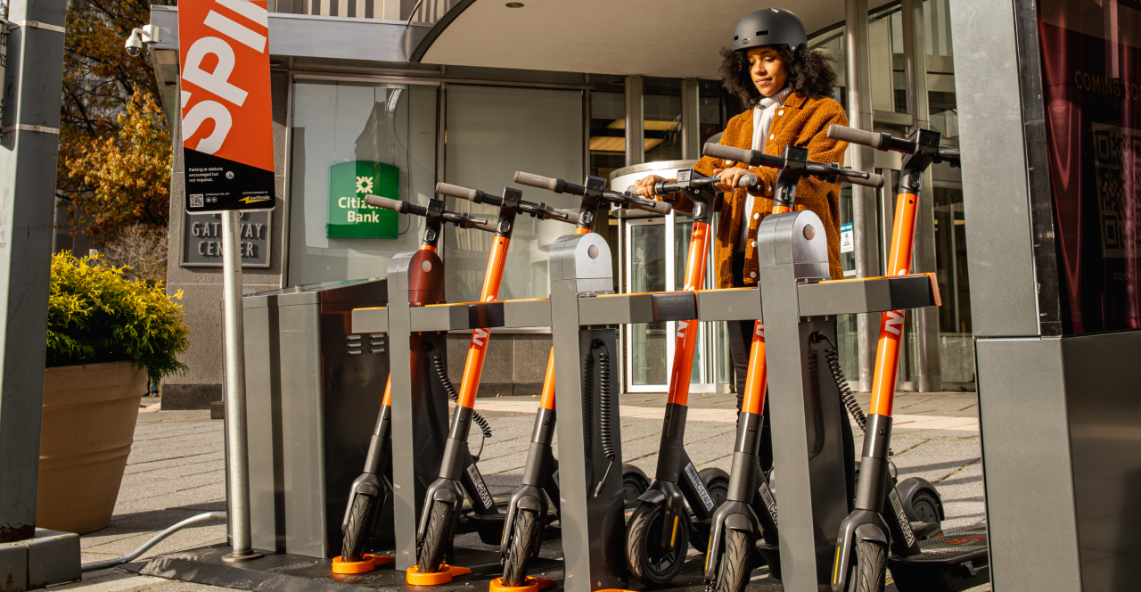 Young woman wearing a black helmet parking a Spin electric scooter at a Spin Hub charging station.