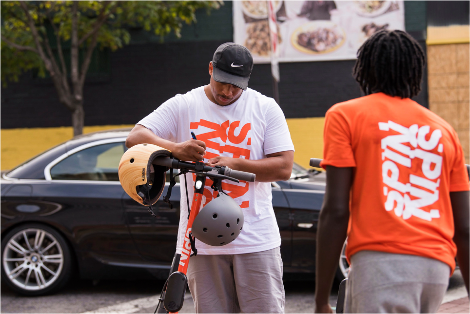 Two Spin team members setting up a scooter