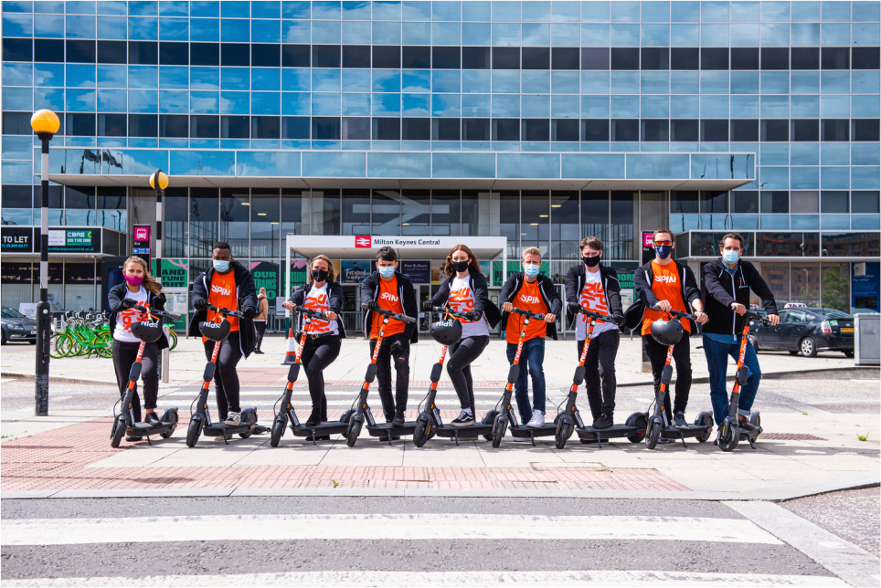 Many people posing with Spin Scooters outside a train station