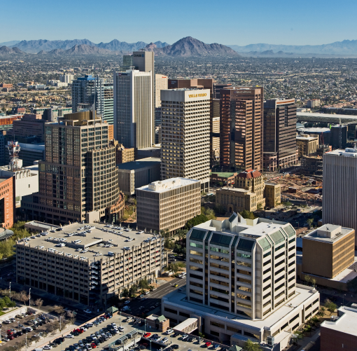 Cities: Aerial view of downtown Phoenix with mountains in the distance.