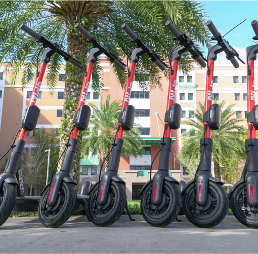 Universities:  Profile view of six Spin electric scooters in front of a large sand-colored building surrounded by palm trees