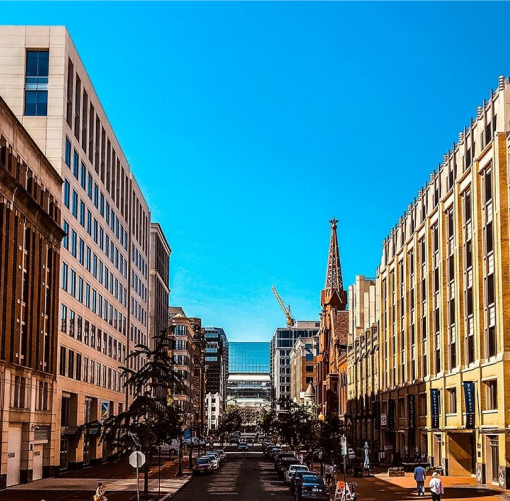Real estate: City street lined by large buildings on a sunny day