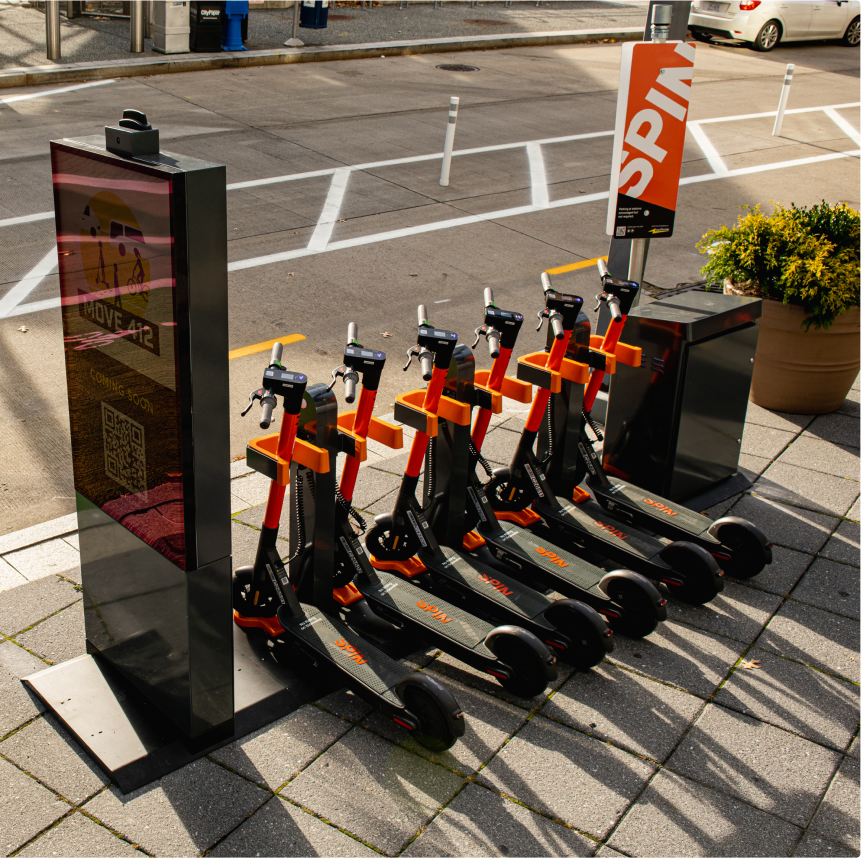 Spin hubs: Group of Spin electric scooters parked at a Spin Hub charging station