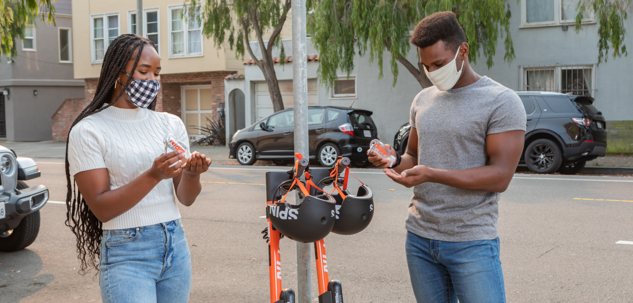 A young man and woman applying hand sanitizer on a city sidewalk in front of several parked Spin electric scooters