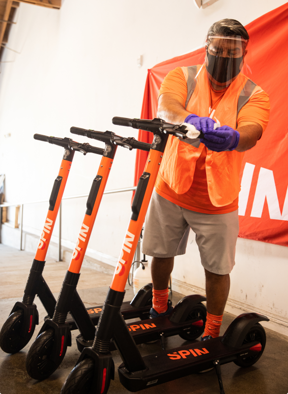 A masked Spin employee sanitizing the handlebars of an electric scooter
