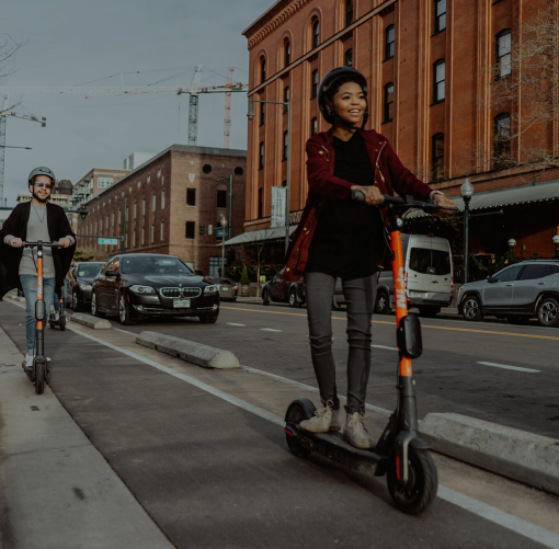 Two people riding Spin scooters in a bike lane