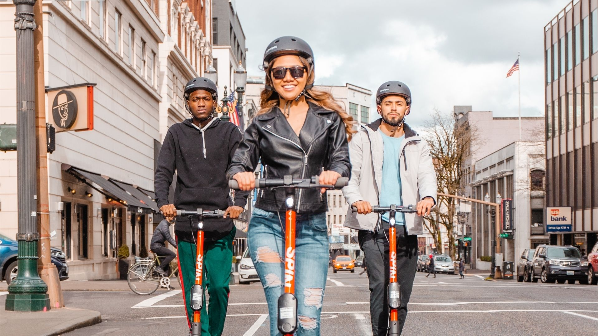 Three young people wearing helmets and riding Spin electric scooters in a triangle formation toward camera
