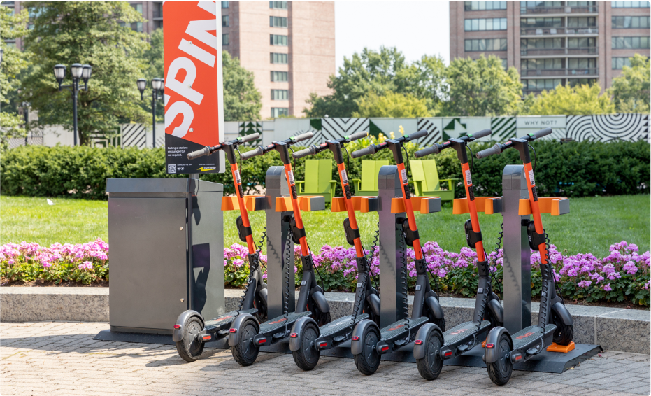 Profile view of six Spin electric scooters in front of a large sand-colored building surrounded by palm trees