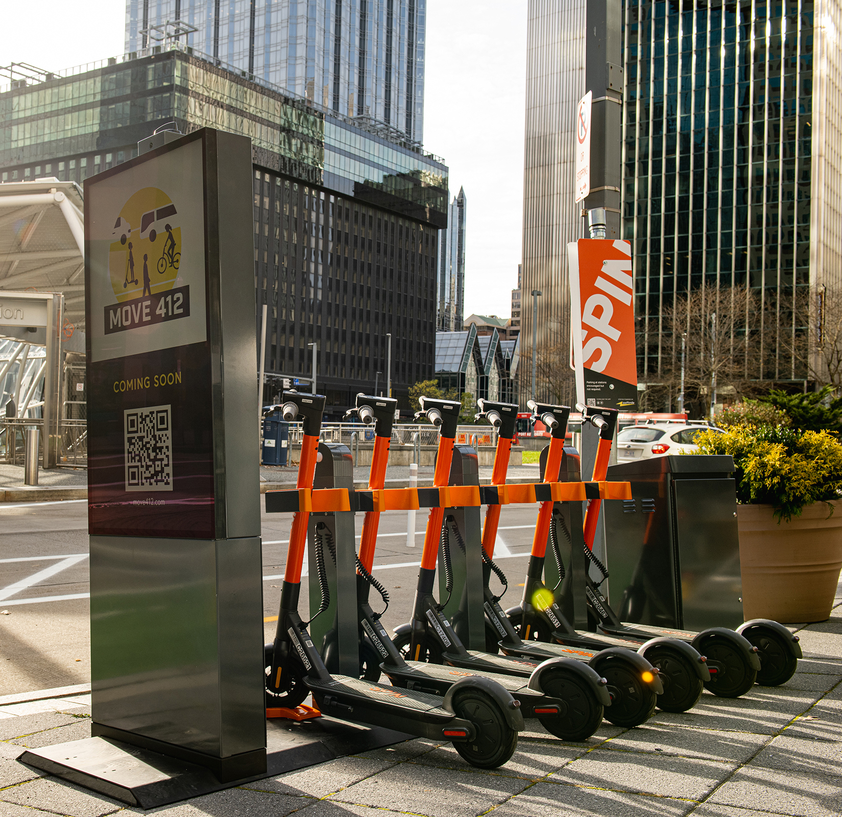 Group of Spin electric scooters parked at a Spin Hub charging station